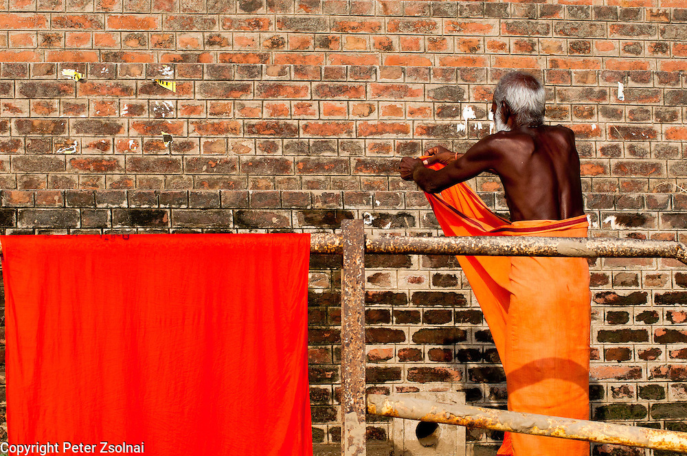 An eldre person is getting dressed on the shore of the Ganges after having his ritual bath in the river.
