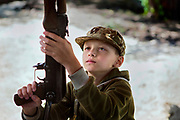 A young boy participating to the ultra-nationalistic Azovets children's camp is holding a kalashnikov rifle and learning about its basic maintenance and care, on the banks of the Dnieper river in Kiev, Ukraine's capital.