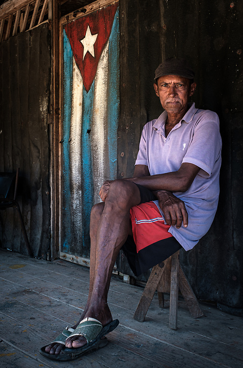 BARACOA, CUBA - CIRCA JANUARY 2020: Portrait of man in front of old wooden door painted with a Cuban Flag in Boca de Yumuri, a hamlet close to Baracoa in Cuba.
