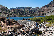 A hiker at West Lake in Hoover Wilderness of Humboldt-Toiyabe National Forest, Eastern Sierra Nevada, Mono County, California, USA. Our backpack from Green Creek Trailhead to Summit Lake was 7.6 mi with 2360 ft gain, 310 ft descent, over a leisurely 3 days, then out on the fourth day. A day hike from our Green Lake campsite to West Lake was 3.9 mi with 1830 ft gain to 8896 ft elev. From Summit Lake, we day hiked east to Burro Pass with a view to Virginia Lakes (2180 ft gain over 4 miles round trip).