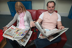 Couple reading newspapers in a library.