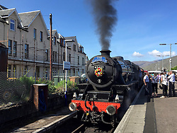 © Licensed to London News Pictures. 12/06/2015. Fort William, UK. The Jacobite steam train carries a floral tribute to Charles Kennedy whilst the funeral of ex-Liberal Democrat leader Charles Kennedy taking place at St John's Church in Caol, near his Fort William home in Scotland on Friday, June 12, 2015. Mr Kennedy died suddenly on June 1, 2015 at the age of 55 after suffering a major haemorrhage as a result of a long battle with alcoholism. Photo credit: Tolga Akmen/LNP