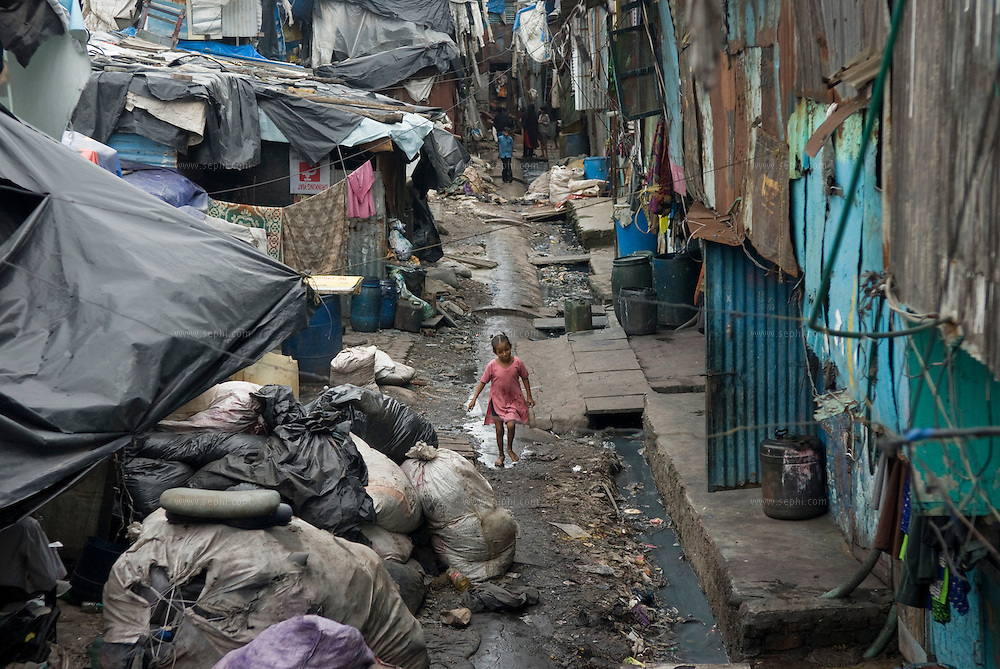 A girl walks on the main water pipe that carries drinking water to Mumbai, as industrial effluent flows next to it. Most of Dharavi homes have no access to piped drinking water.
