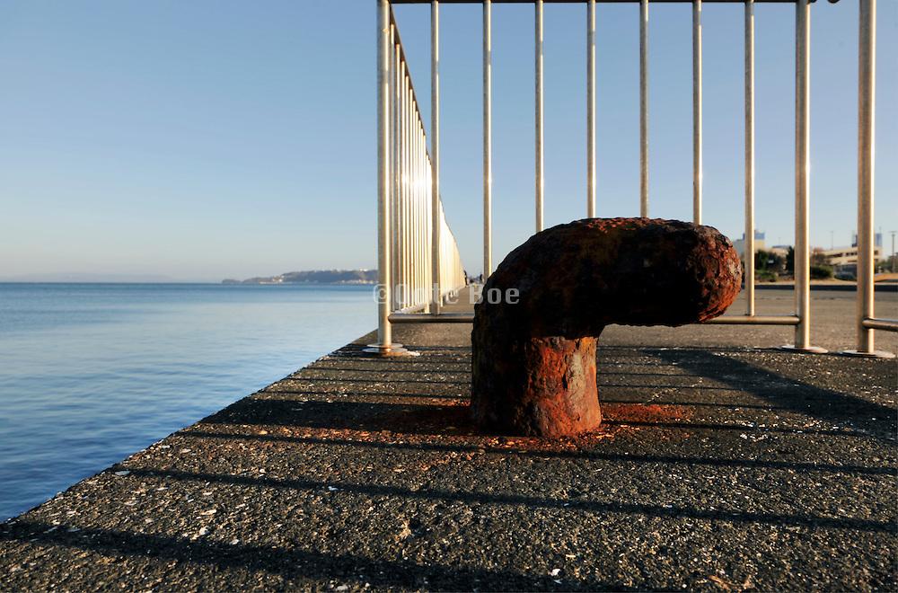 rusty bollard on fenced off pier Tokyo bay