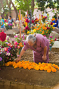 An elderly woman decorates the grave of a loved one with flowers in honor of the deceased at the San Antonino Castillo cemetery during the Day of the Dead Festival known as Día de Muertos on November 3, 2013 in San Antonino Castillo Velasco, Oaxaca, Mexico.