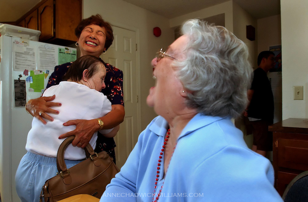 """Irene Pinole, 76, hugs Lita Acacio, her former caregiver and someone she calls """"mom"""", after being reunited with her sister, Olga Johnson, right, after a 65-year hiatus."""