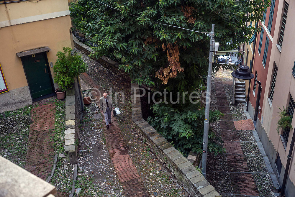 An elderly man walks through a residential district of the mediaeval centre of Genoa, Italy.