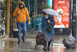 © Licensed to London News Pictures. 04/06/2021. London, UK. An elderly woman shelters from the rain beneath an umbrella during rainfall in north London. According to The Met Office, more rain is expected today across London and the South East of England, with the hot weather returning tomorrow. Photo credit: Dinendra Haria/LNP