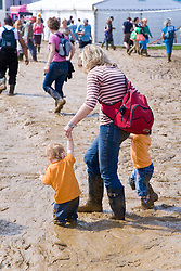 Young family of forced to wear Wellington boots when heavy rain brings muddy ground at WOMAD (World of Music; Arts and Dance) Festival; Charlton Park; Malmesbury; 2007,