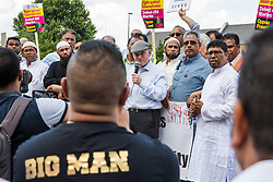 London, UK. 12 July, 2019. John Biggs, the Labour Mayor of Tower Hamlets, addresses a member of the local community (wearing the Big Man t-shirt) who criticised him during a protest close to the site where Youness Bentahar, aged 38, was violently arrested by Metropolitan Police officers on 10th July following a 5-stage warning. The incident, during which Mr Bentahar appeared to be having a seizure, has since been referred to the Metropolitan Police's Central East Command Professional Standards Unit after a video of the arrest went viral on social media. Mr Bentahar was filmed being struck with handcuffs and pinned down by police officers after he had stopped on a single yellow line with a disabled badge displayed and ignored the five-stage warning.