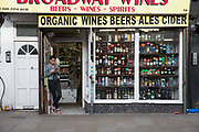 A woman uses her mobile phone outside an off licence on Broadway Market on 27th May 2017 in London, United Kingdom. Broadway Market is an East London street running from London Fields to the Regents Canal in the London Borough of Hackney. From the series Our Small World, an observation of our mobile phone obsessions