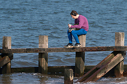 Portobello, Scotland, UK. 25 April 2020. Views of people outdoors on Saturday afternoon on the beach and promenade at Portobello, Edinburgh. Good weather has brought more people outdoors walking and cycling. The beach appears busy with possibly a breakdown in social distancing happening later in the afternoon. Solitary man listening to music sitting on a wooden groyne.  Iain Masterton/Alamy Live News