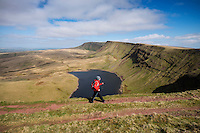 Female hill walker hiking towards Waun Lefrith above Llyn Y Fan Fach, Black Mountain, Brecon Beacons national park, Wales