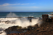 Pacific Ocean waves crash into the rugged coast at Lawa'i Bay in southern Kauai.