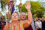 15 APRIL 2011 - PHOENIX, AZ: CHRISTINA RASTERZ, from Glendale, AZ, prays at the opening of the Tea Party rally in Phoenix Friday. About 500 supporters of the Tea Party movement rallied Friday at the Arizona State Capitol to mark tax day. They protested high taxes, the federal deficit, the debt limit and immigration policy. About 50 pro-immigrant protesters held a counter rally at the capitol. At least one person was arrested, and others led away by police after several shouting matches between Tea Party supporters and the immigrants rights protesters broke out.     Photo by Jack Kurtz
