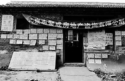 Real estate office selling new apartments in old hutong area where houses are being demolished in Beijing China