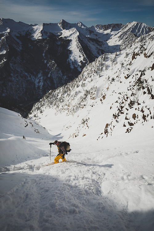 Maxwell J Morrill ascends the upper chute of Tanner's Couloir for a backcountry snowboard descent, Wasatch Mountains, Utah.