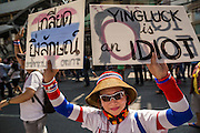 22 DECEMBER 2013 - BANGKOK, THAILAND: A woman holds up a sign critical of Thai Prime Minister Yingluck Shinawatra. Hundreds of thousands of Thais gathered in Bangkok Sunday in a series of protests against the caretaker government of Yingluck Shinawatra. The protests are a continuation of protests that started in early November and have caused the dissolution of the Pheu Thai led government of Yingluck Shinawatra. Protestors congregated at home of Yingluck and launched a series of motorcades that effectively gridlocked the city. Yingluck was not home when protestors picketed her home.     PHOTO BY JACK KURTZ