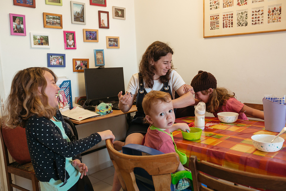 Twin girls Clil (R) and Alma (L), their brother Ofek, and mother Anna Michel, are seen during breakfast, at their home in Jerusalem, Israel, on May 3, 2020.