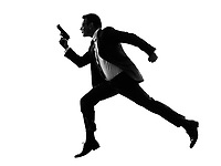 one caucasian man running with handgun in silhouette on white background
