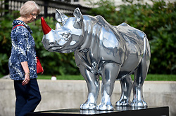 **CAPTION CORRECTION - Rhino statues are 750mm tall, not 750cm tall, as stated in previous captions**<br /> © Licensed to London News Pictures. 20/08/2018. LONDON, UK. A woman views a rhino by Gerry McGovern in Trafalgar Square.  At 750mm tall and weighing 300 kg, each rhino has been specially embellished by an internationally renowned artist.  21 rhinos are in place at a popular location in central London, forming the Tusk Rhino Trail, until World Rhino Day on 22 September to raise awareness of the severe threat of poaching to the species' survival.  They will then be auctioned by Christie's on 9 October to raise funds for the Tusk animal conservation charity.  Photo credit: Stephen Chung/LNP