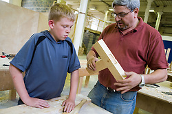 Teacher checking students tenon and mortice joint in woodwork class,