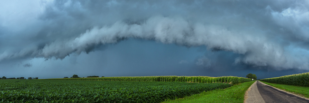 I wasn't expecting to see such a scene on this day, since the storm chances were low. But once I heard the thunder rumbling at 11am, I quickly left the house. After driving southeast I let the storm overtake me near the town of Kenney, and shot this panorama shortly before it started raining.  This time of year the corn is often 8 feet tall which restricts the view of approaching storms. I have to look for somewhere else to shoot such as this field of soybeans.<br /> <br /> Date Taken: July 14, 2014