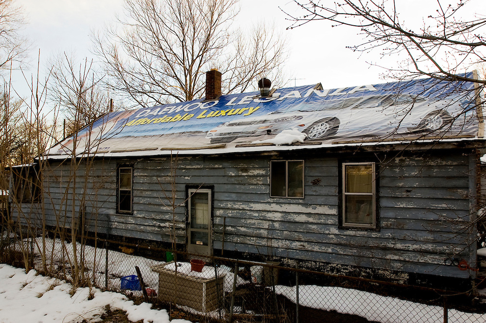Matt Dixon | The Flint Journal..After her roof had been leaking for years, Sharon Dickinson payed $90 for a a banner to cover her roof. The roof has since stopped leaking.