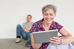 Mature woman using digital tablet while mature man sitting in background