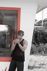 man in a tank top lighting a cigarette by a 50's style building