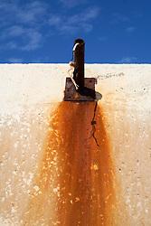 Particolare del porto di Brindisi. Un tubo arruginito, una volta un lampione, contrasta con i toni rossi della sua ruggine con il blu intenso del cielo terso.