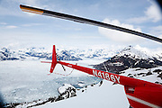 A helicopter sits on a ridge above Columbia Bay, near Valdez, Alaska. The current terminus of the Columbia Glacier is visible in the distance.