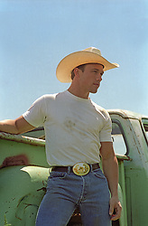 handsome young All American Cowboy standing by a truck outdoors
