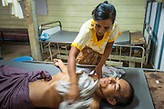 20 MAY 2013 - MAE KASA, TAK, THAILAND:  A woman helps cool down her husband, who has malaria, in the intensive care room of the SMRU clinic in Mae Kasa, Thailand. Health professionals are seeing increasing evidence of malaria resistant to artemisinin coming out of the jungles of Southeast Asia. Artemisinin has been the first choice for battling malaria in Southeast Asia for 20 years. In recent years though,  health care workers in Cambodia and Myanmar (Burma) are seeing signs that the malaria parasite is becoming resistant to artemisinin. Scientists who study malaria are concerned that history could repeat itself because chloroquine, an effective malaria treatment until the 1990s, first lost its effectiveness in Cambodia and Burma before spreading to Africa, which led to a spike in deaths there. Doctors at the Shaklo Malaria Research Unit (SMRU), which studies malaria along the Thai Burma border, are worried that artemisinin resistance is growing at a rapid pace. Dr. Aung Pyae Phyo, a Burmese physician at a SMRU clinic just a few meters from the Burmese border, said that in 2009, 90 percent of patients were cured with artemisinin, but in 2010, it dropped to about 70 percent and is now between 55 and 60 percent. He said the concern is that as it becomes more difficult to clear the parasite from a patient, progress that has been made in combating malaria will be lost and the disease could make a comeback in Southeast Asia.    PHOTO BY JACK KURTZ