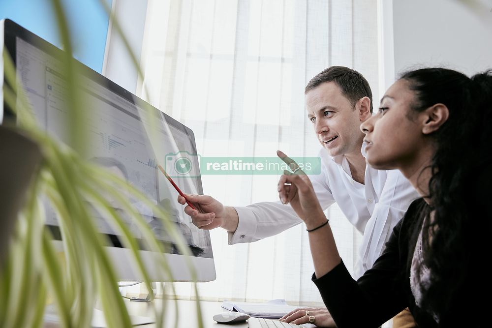 January 19, 2018 - Man and woman discussing data on a large computer screen (Credit Image: © Mint Images via ZUMA Wire)