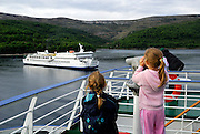 Two children (9 years old, 5 years old) on boat, looking through pay-telescope at inter-island ferry. Near island of Korcula, Adriatic Sea, Croatia