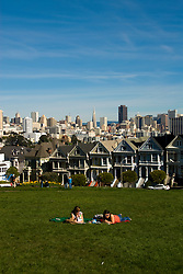 California: San Francisco. People relaxing in Alamo Square with view of Victorians and modern downtown. Photo copyright Lee Foster. Photo #: san-francisco-alamo-square-20-casanf77486