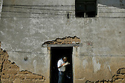 A man reads a book on the threshold of his home in Chichicastanango, Guatemala.