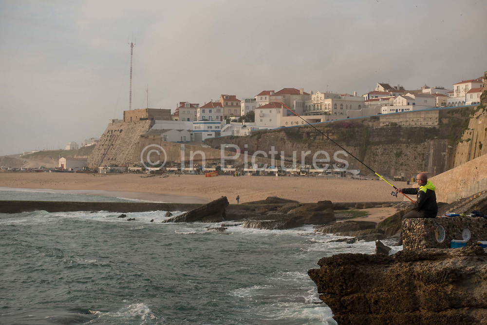 A man fishing off the coast of Praia dos Pescadores on 24th May 2018 in Ericeira in Portugal. Ericeira is a civil parish and seaside resort/fishing community on the western coast of Portugal.