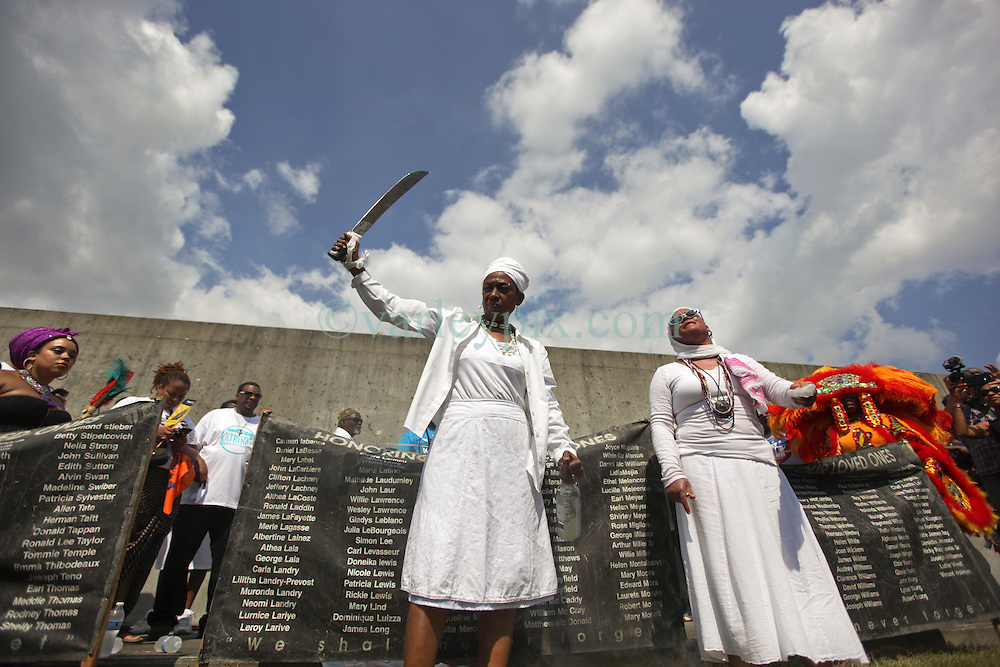 29 August 2015. Lower 9th Ward, New Orleans, Louisiana.<br /> Hurricane Katrina 10th anniversary memorials.<br /> Mourners conduct a ritual to remember those who perished during the storm. The ceremony is conducted close to where a barge broke through the levee a decade earlier causing widespread flooding and loss of life. <br /> Photo credit©; Charlie Varley/varleypix.com.