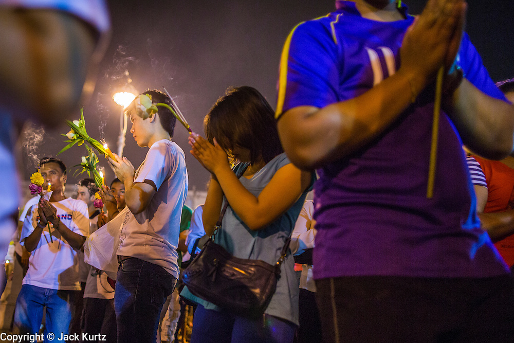 """25 FEBRUARY 2013 - BANGKOK, THAILAND:  Thais stop to pray during a candle light procession around Wat Benchamabophit Dusitvanaram (popularly known as either Wat Bencha or the Marble Temple) on Makha Bucha Day. Thais visit temples throughout the Kingdom on Makha Bucha Day to make merit and participate in candle light processions around the temples. Makha Bucha is a Buddhist holiday celebrated in Myanmar (Burma), Thailand, Cambodia and Laos on the full moon day of the third lunar month (February 25 in 2013). The third lunar month is known in Thai is Makha. Bucha is a Thai word meaning """"to venerate"""" or """"to honor"""". Makha Bucha Day is for the veneration of Buddha and his teachings on the full moon day of the third lunar month. Makha Bucha Day marks the day that 1,250 Arahata spontaneously came to see the Buddha. The Buddha in turn laid down the principles his teachings. In Thailand, this teaching has been dubbed the 'Heart of Buddhism'.     PHOTO BY JACK KURTZ"""