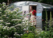© Licensed to London News Pictures. 21/05/2012. Chelsea, UK. Garden designer Jo Thompson in the 'Caravan Club' garden she designed. Press preview of The Chelsea Flower Show today 21 May 2012. The world's most famous flower show, which has been held in the grounds of the Royal Chelsea Hospital since 1913, will be open to the public from Tuesday. Visitors are expected to flock in their thousands to see displays of plants, flowers and furniture for ideas on how to decorate their gardens.. Photo credit : Stephen Simpson/LNP