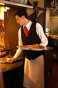 A waiter with several plates of grille meat and potatoes that will be served to customers., in the restaurant El Palenque, the sword fish swordfish, in the Mercado del Puerto, the market in the port harbour harbor where many people go and eat and shop on weekends Montevideo, Uruguay, South America