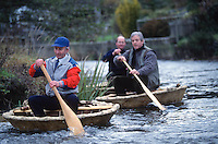 men sailing hand built traditional coracles on river