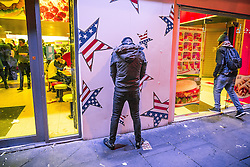 © Licensed to London News Pictures . 01/01/2016 . Manchester , UK . A man urinates up against a fast food takeaway wall . Revellers in Manchester on a New Year night out at the clubs around the city centre's Printworks venue . Photo credit : Joel Goodman/LNP
