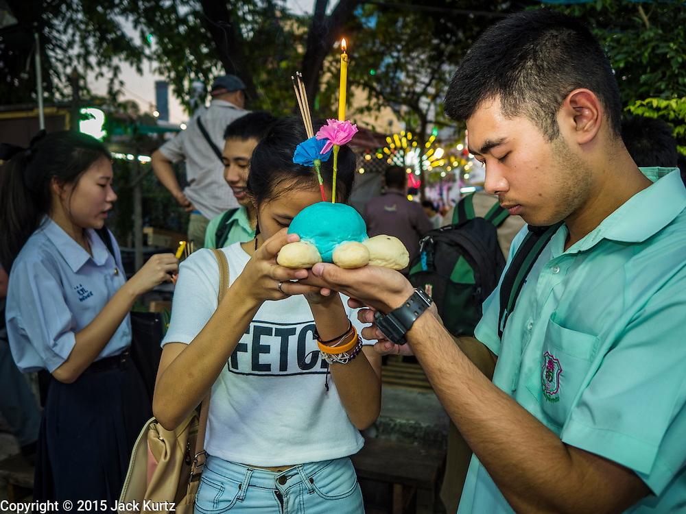 25 NOVEMBER 2015 - BANGKOK, THAILAND:  Thais pray before floating their krathong during Loy Krathong at Wat Yannawa in Bangkok. Loy Krathong takes place on the evening of the full moon of the 12th month in the traditional Thai lunar calendar. In the western calendar this usually falls in November. Loy means 'to float', while krathong refers to the usually lotus-shaped container which floats on the water. Traditional krathongs are made of the layers of the trunk of a banana tree or a spider lily plant. Now, many people use krathongs of baked bread which disintegrate in the water and feed the fish. A krathong is decorated with elaborately folded banana leaves, incense sticks, and a candle. A small coin is sometimes included as an offering to the river spirits. On the night of the full moon, Thais launch their krathong on a river, canal or a pond, making a wish as they do so.    PHOTO BY JACK KURTZ
