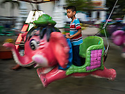 21 NOVEMBER 2015 - BANGKOK, THAILAND: A boy rides a merry-go-round at the Wat Saket temple fair. Wat Saket is on a man-made hill in the historic section of Bangkok. The temple has golden spire that is 260 feet high which was the highest point in Bangkok for more than 100 years. The temple construction began in the 1800s in the reign of King Rama III and was completed in the reign of King Rama IV. The annual temple fair is held on the 12th lunar month, for nine days around the November full moon. During the fair a red cloth (reminiscent of a monk's robe) is placed around the Golden Mount while the temple grounds hosts Thai traditional theatre, food stalls and traditional shows.     PHOTO BY JACK KURTZ