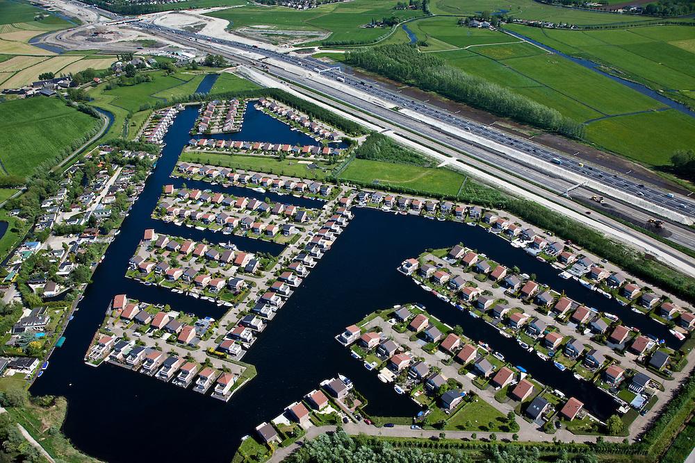 Nederland, Utrecht, Abcoude, 20-03-2009; verbreden van Rijksweg A2 ter hoogte van Abcoude. Om de doorstroming op de A2 structureel te verbeteren wordt de snelweg verbreed van 2x3 naar 2x5 rijstroken. Westelijk van de weg (onder) Buitenborgh, villapark met recreatiewoningen. Hoewel het bestemmingsplan (streekplan) bouw in dit deel van het Groene Hart verbiedt, mochten deze woningen wel gebouwd omdat ze (op papier) niet permanent bewoond worden. De A2 tussen het knooppunt Holendrecht en Maarssen is een van de knelpunten die versneld wordt aangepakt om de economische schade ten gevolge van de files te bepreken. De versnelde aanpak is het mogelijk dankzij een speciale Spoedwet . Air view on holiday houses near the motorway A2, the main road in the Netherlands, between Amsterdam en Utrecht. .Swart collectie, luchtfoto (toeslag); Swart Collection, aerial photo (additional fee required).foto Siebe Swart / photo Siebe Swart
