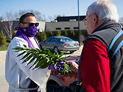 "05 APRIL 2020 - DES MOINES, IOWA:  Rev. RUSSELL LACKEY, left, follows ""Social Distancing"" guidelines while he hands out palms during a drive through Palm Sunday service sponsored by Luther Memorial Church on the campus of Grand View University in Des Moines. About 150 people attended the service. They remained in their cars while the ministers read a short passage from the Bible, handed out palms and blessed them. On Sunday, 05 April, Iowa reported 868 confirmed cases of the Novel Coronavirus (SARS-CoV-2) and COVID-19. There have been 22 deaths attributed to COVID-19 in Iowa. Restaurants, bars, movie theaters, places that draw crowds are closed until 30 April. The Governor has not ordered ""shelter in place"" but several Mayors, including the Mayor of Des Moines, have asked residents to stay in their homes for all but essential needs. People are being encouraged to practice ""social distancing"" and many businesses are requiring or encouraging employees to telecommute.          PHOTO BY JACK KURTZ"