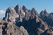 """The peaks of the Cadini Group jut high in the Dolomites range near Cortina d'Ampezzo, Veneto region, Italy, Europe. In the Cadini di Misurina, Cima Grande rises to 2999 meters (9839 feet), between Cima Piccola 2857 m (9373 ft) and Cima Ovest or """"Western Peak"""" 2973 m (9754 ft). The Dolomites are part of the Southern Limestone Alps, in northern Italy, Europe. UNESCO honored the Dolomites as a natural World Heritage Site in 2009."""